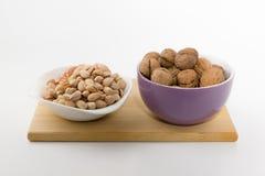 Tellervolle der verschiedenen Nüsse stehen auf einer Platte auf einem weißen backgrou Stockbild