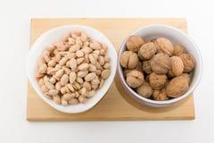 Tellervolle der verschiedenen Nüsse stehen auf einer Platte auf einem weißen backgrou Lizenzfreie Stockfotografie