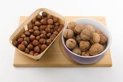 Tellervolle der verschiedenen Nüsse stehen auf einer Platte auf einem weißen backgrou Lizenzfreies Stockfoto