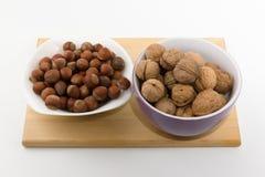 Tellervolle der verschiedenen Nüsse stehen auf einer Platte auf einem weißen backgrou Lizenzfreie Stockfotos