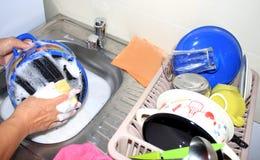 Tellerwäsche durch Frau im Haus Stockbild