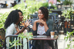 Telling funny story. Pretty African-American women telling story to her female friend Royalty Free Stock Photos