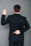 Telling lies. Rear view of young businessman keeping his fingers crossed and arm raised while standing against grey background Royalty Free Stock Photography