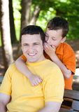Telling a secret. A boy is sharing a secret with his father Royalty Free Stock Image