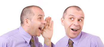 Telling a secret. Business man telling a secret to himself isolated on white background stock photos