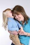 Telling Secrets. Beautiful blonde little girl telling teen girl a secret Stock Photos