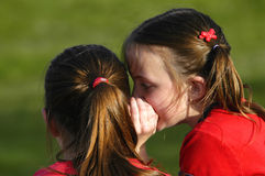Telling Secrets. Two young girls in red whispering secrets to each other Royalty Free Stock Photos