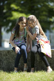 Telling secrets. Two little girls whispering secrets while sitting outdoors Stock Image