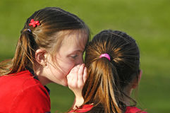 Telling Secrets. Two girls telling secrets outdoors at the park Royalty Free Stock Image