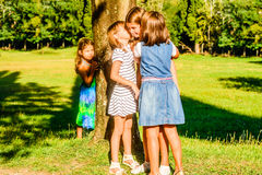 Telling secrets. Four little girls playing in the park and whispering secrets Stock Image
