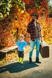 Telling stories about past times. Father with suitcase and his son. Bearded dad telling son about travelling. Traveler stock photography