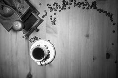 Telling story from the past - old vintage retro grinder with ground coffee and cup of black coffee with coffee beans top view Royalty Free Stock Photo