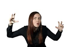 Telling a terrible story. Girl on a white background frightens the viewer, taking a menacing pose and making a terrible face Royalty Free Stock Photos