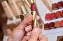 Tem um batom vermelho fêmea Mão fêmea com cor vermelha do batom vermelho e os batons diferentes de teste, mostrando as amostras d Imagens de Stock