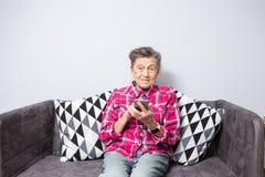 Temaåldringen använder teknologi den gamla gråhåriga Caucasian kvinnan med skrynklor sitter hemmet i vardagsrum på soffan och royaltyfria foton