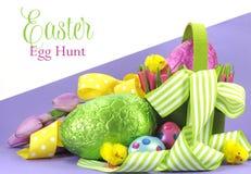 Tema brillante feliz de la caza del huevo de Pascua del color de Pascua con las cintas y la cesta amarillas, verdes de huevos Foto de archivo libre de regalías