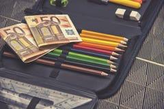 Tema caro da escola, caixa de lápis com euro- dinheiro Fotos de Stock