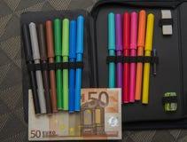 Tema costoso de la escuela, caja de lápiz con el dinero euro Foto de archivo libre de regalías