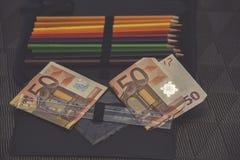 Tema costoso de la escuela, caja de lápiz con el dinero euro Fotos de archivo libres de regalías