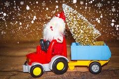 Tema da celebração do feriado do Natal Santa Claus leva a árvore de Natal no trator com reboque Fotos de Stock Royalty Free