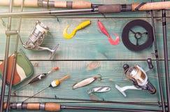 Tema da pesca O quadro das varas de pesca com equipamentos de pesca, a linha, o carretel e a pesca buoy no fundo de madeira verde Imagens de Stock Royalty Free