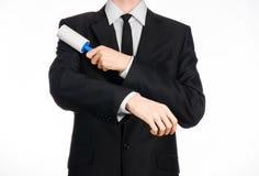 Tema da tinturaria e do negócio: um homem em um terno preto que guarda uma escova pegajosa azul para a roupa de limpeza e a mobíl Fotografia de Stock