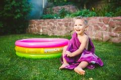 Tema das férias de verão Um menino caucasiano da criança de 3 anos pequena que joga no quintal de uma casa na grama perto de um c imagens de stock royalty free