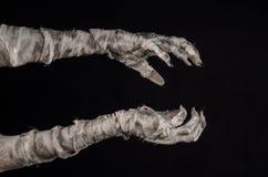 Tema de Halloween: viejas manos terribles de la momia en un fondo negro Foto de archivo