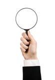 Tema de la búsqueda del negocio: el hombre de negocios en un traje negro que sostenía una lupa en un blanco aisló el fondo Fotos de archivo