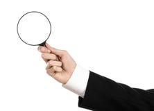 Tema de la búsqueda del negocio: el hombre de negocios en un traje negro que sostenía una lupa en un blanco aisló el fondo Fotos de archivo libres de regalías