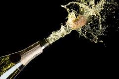 Tema de la celebración con la explosión de salpicar el vino espumoso del champán en fondo negro Imagenes de archivo