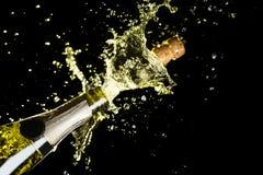 Tema de la celebración con la explosión de salpicar el vino espumoso del champán en fondo negro Foto de archivo
