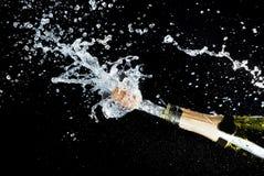 Tema de la celebración con la explosión de salpicar sparklin del champán Fotos de archivo libres de regalías