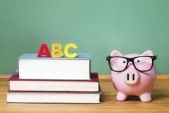 Tema de la escuela con ABCs y hucha rosada con la pizarra en el fondo Fotos de archivo