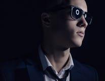 Tema de la moda de los hombres: hombre joven hermoso en un traje elegante y las gafas de sol que se colocan en un fondo oscuro en fotos de archivo libres de regalías