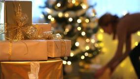 Tema de la Navidad La mujer joven pone los regalos debajo del árbol de navidad almacen de metraje de vídeo