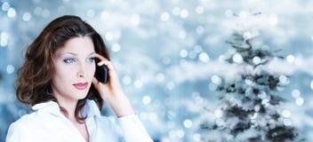 Tema de la Navidad, mujer de negocios que usa smartphone en bergantín borroso Foto de archivo libre de regalías