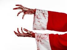 Tema de la Navidad y de Halloween: Mano sangrienta de Santa Zombie en un fondo blanco Foto de archivo