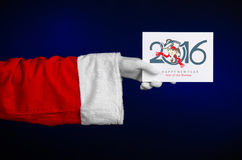 Tema 2016 de la Navidad y del Año Nuevo: Mano de Santa Claus que sostiene un carte cadeaux blanco en un fondo azul marino en estu Fotografía de archivo libre de regalías