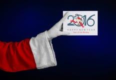 Tema 2016 de la Navidad y del Año Nuevo: Mano de Santa Claus que sostiene un carte cadeaux blanco en un fondo azul marino en estu Foto de archivo