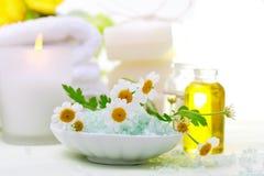Tema de la relajación del balneario con las flores, la sal de baño, el aceite esencial y las velas Imágenes de archivo libres de regalías