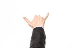 Tema de los gestos y del negocio: el hombre de negocios muestra gestos de mano con un de primera persona en un traje negro en un  Imagen de archivo