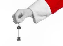 Tema de Santa Claus: Dé a controles de santa las llaves a un nuevo apartamento o a una nueva casa de un fondo blanco Imágenes de archivo libres de regalías