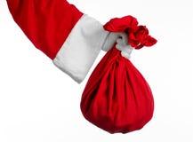 Tema de Santa Claus: Papá Noel que sostiene un saco rojo grande con los regalos en un fondo blanco Imágenes de archivo libres de regalías