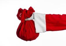 Tema de Santa Claus: Papá Noel que sostiene un saco rojo grande con los regalos en un fondo blanco Foto de archivo