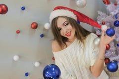 Tema del Año Nuevo Una muchacha rubia hermosa en un sombrero rojo de Santa Claus y un suéter hecho punto blanco abrió su hombro a fotografía de archivo libre de regalías