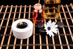 Tema del balneario con las velas y las flores en fondo negro Foto de archivo libre de regalías