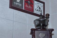 Tema del café en mural decorativo y la amoladora de café manual antigua vieja en fondo de la pared tejada ligera foto de archivo libre de regalías