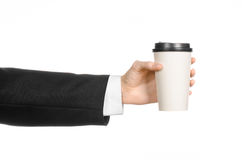 Tema del caffè dei pranzi di lavoro: uomo d'affari in un vestito nero che tiene una tazza di caffè bianca della carta in bianco c Immagini Stock Libere da Diritti