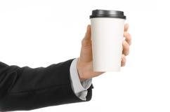 Tema del caffè dei pranzi di lavoro: uomo d'affari in un vestito nero che tiene una tazza di caffè bianca della carta in bianco c Fotografia Stock Libera da Diritti